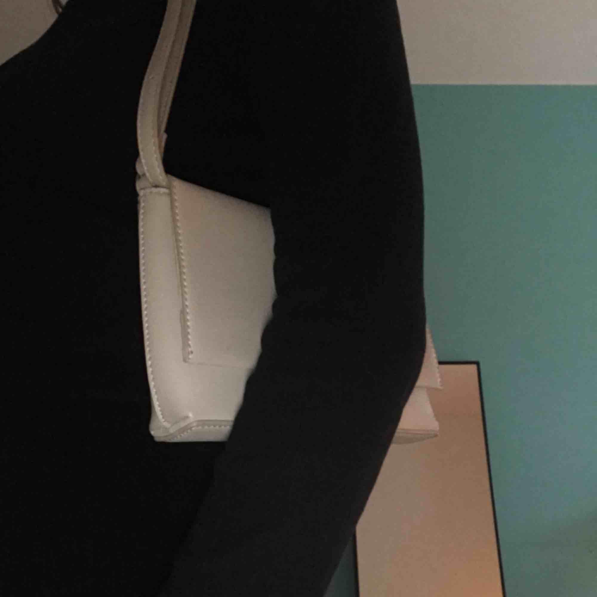 Snygg gråaktig handväska med ett spänne av silver. Axelbandet är justerbart och instoppat i väskan. Använd några gånger men ser helt ny ut, flera fickor finns även inuti väskan.😊ä. Väskor.