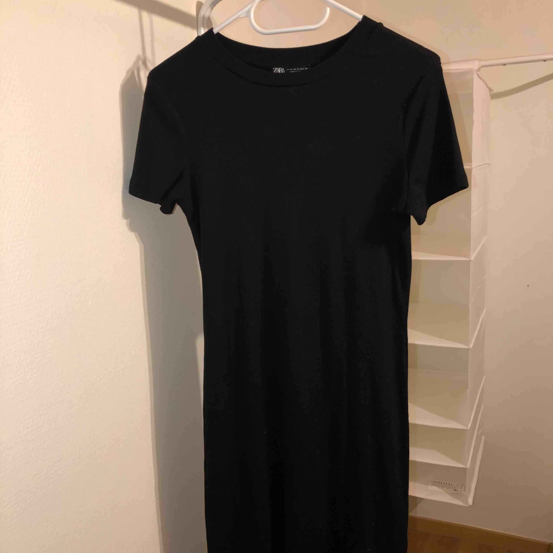 En lång basic svart kortarmad klänning, köpt på Zara. Säljes pga: Använder aldrig. Klänningar.