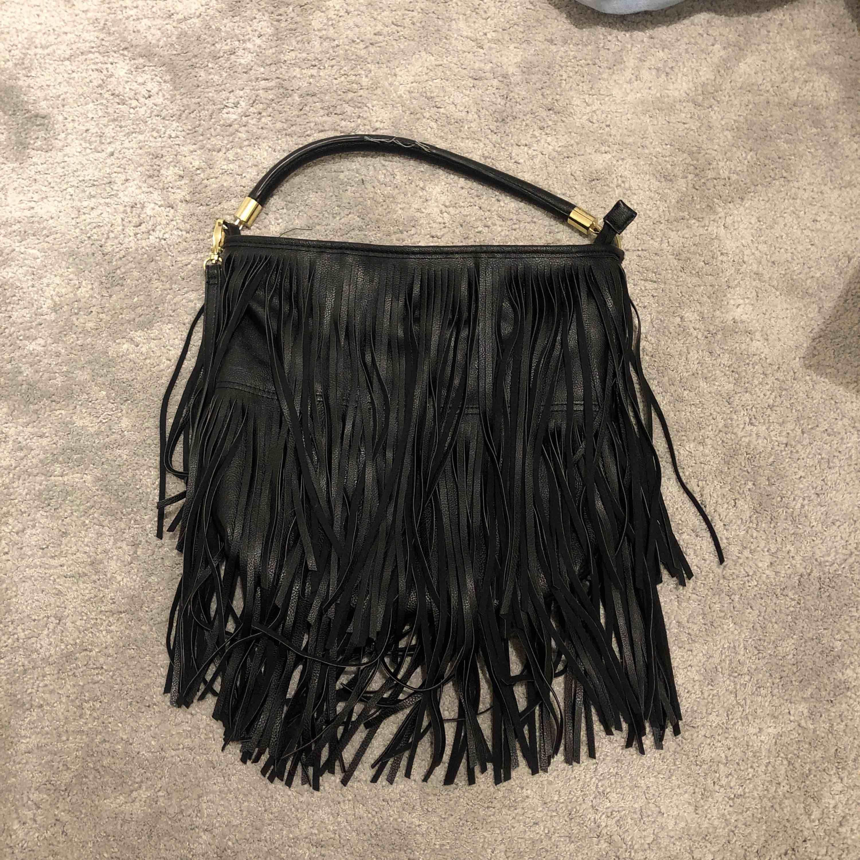 """En väska med fransar från HM som inte säljs längre.  Den har ett litet fack inuti och är lite """"skadad"""" på handtaget⚡️ Det finns två band, ett kort och ett långt som går att ta på/av🥰 Frakt ingår inte i priset🎸. Väskor."""