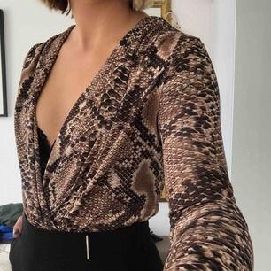 Snygg body i med ormmömster från Zara. Urringningen är enkelt justerbar. Frakt på 45kr tillkommer.