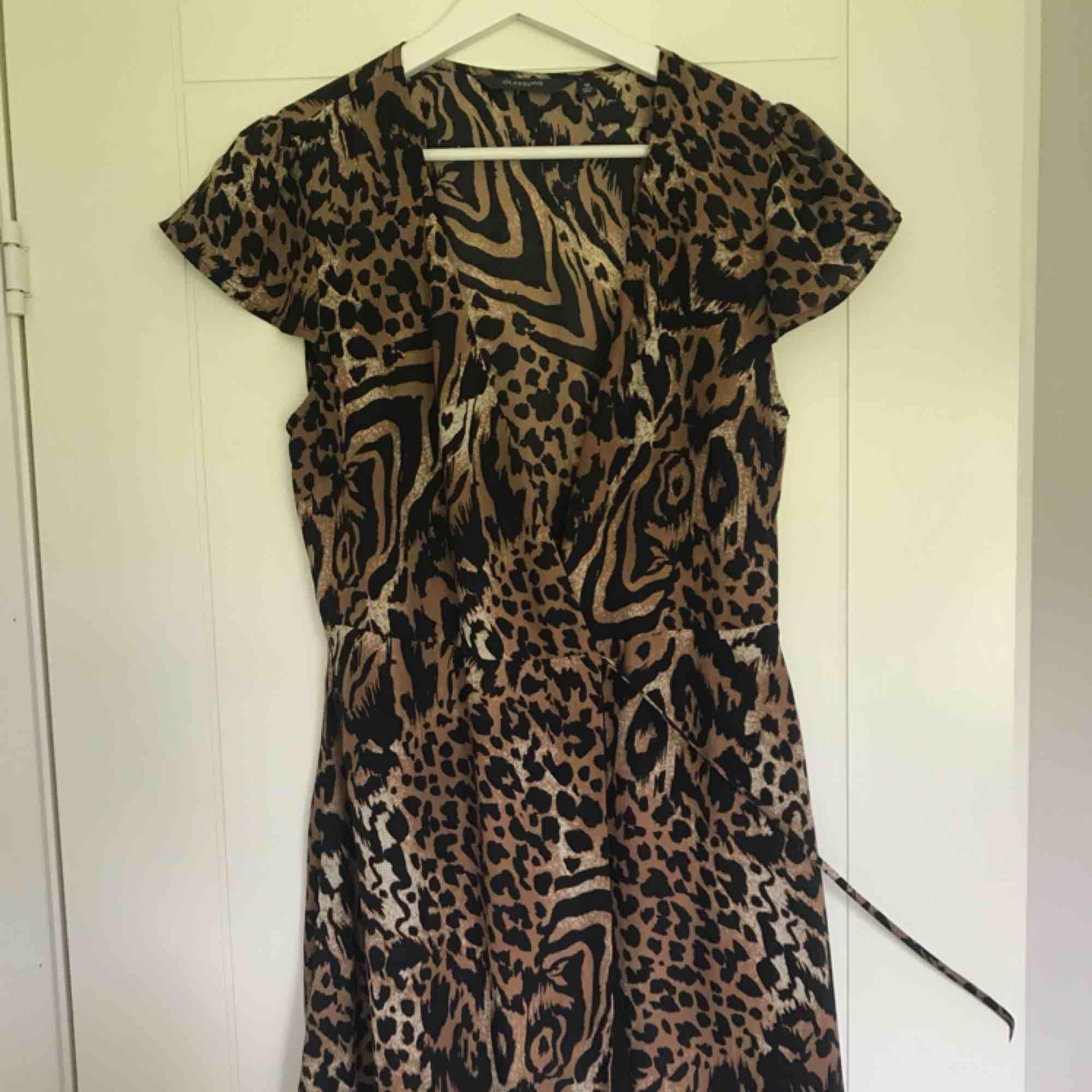 Klänning i leopard och knytning i midjan. V-ringad och skönt material. Mycket bra skick!. Klänningar.