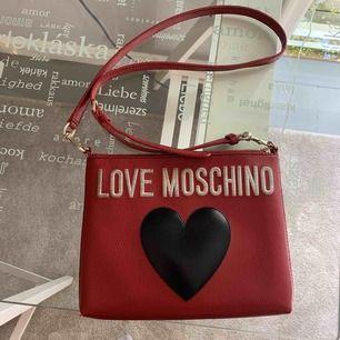 En liten röd LOVE MOSCHINO väska. Axelbandet är reglerbart och väskan är i bra skick. De vita bokstäverna är lite smutsiga men ingenting som inte kan gå bort. Bra storlek som får plats med det viktigaste.