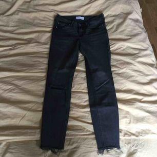 Mörkgrå jeans. Avklippta, slutar ovanför anklarna. Ett hål i höger knä. Modellen har nästan ingen stretch, därför sitter de ganska tajt. Lite större i midjan, men går att lösa med ett skärp.