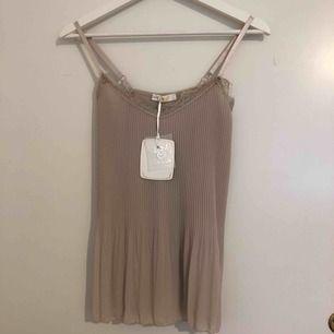 Ett beige linne inköpt i Grekland. Finns ingen storlek på plagget men skulle säga att de är runt en S/ M. Aldrig använd, prislappen sitter kvar. Färgen är som på den andra bilden. Frakt tillkommer.
