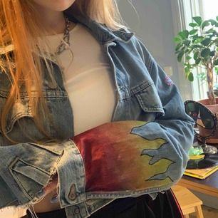 En stor, croppad jeanjacka med eld i slutet på båda ärmarna som jag själv har målat!😊 Den är väldigt cool och skriv bara i kommentarerna om vi ska diskutera priset! frakt ingår inte❤️💜