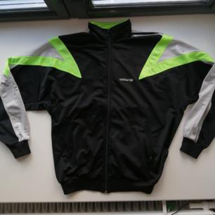 Adidas tröja 90-tals stil, svart med neongröna och silvriga detaljer. Köpt från Humana Second Hand för några år sen. Alla dragkedjor funkar, passformen är oversize men kan vara lite tight i midjan då resåren är ganska hård. Jag skulle säga att den är storlek 36-38.