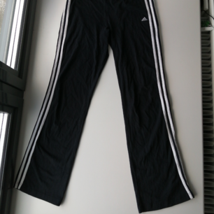 Svarta Adidas träningsbyxor i bomull, köpt på Humana. Retro 90-tals stil med utsvängda ben och hög midja. Super bekväma mjukisbyxor som ger dig Spice Girls looken. Sitter perfekt i midjan resåren är superskön!