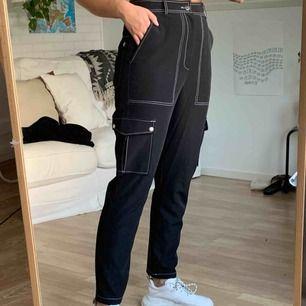 Svarta byxor med vita kontrastsömmar. Använda endast ett par gånger. Finns att hämta i Åkersberga eller frakt 50kr :)