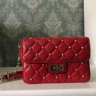 Klarröd / röd väska som inte kommit till användning trots sitt fina utseende. Guldiga detaljer. Inuti finns liten fick med dragkedja. Knäppning utanpå.Mått: 20x12x4,5 cmAxelrem: ca 110cmMärke: ginatricot  Köpare står för frakt. (ligger på ca 45kr)