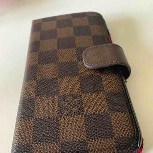 louis vuitton skal plånbok, passar IPhone XR.  Är i god skick. Halv skinn/im. Säljes till bra pris då den är använd , i ca;5 mån!   Köparen står för frakten!