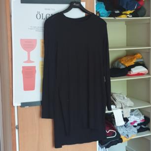 Lång, mjuk tröja i svart med slits på sidorna.