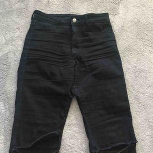 Säljer svarta tajta jeans med hål i på båda sidor. Sitter till naveln på mig som är ca 155. Sitter inte för kort på benen heller.