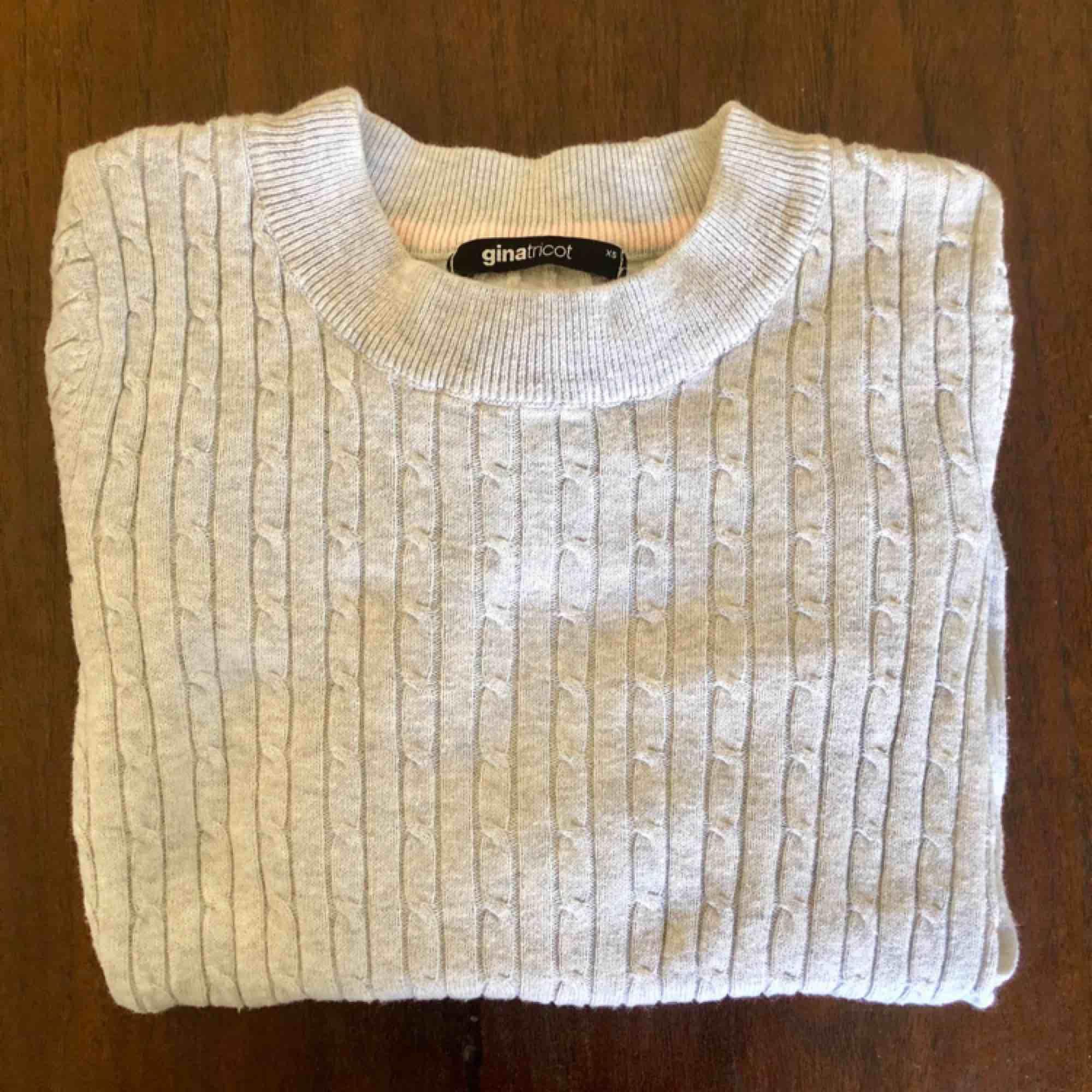 Ljusgrå stickad tröja från Gina Tricot i XS. Smal passform i 100 % ekologisk bomull. Kan mötas upp i centrala Stockholm alt skickas då köpare står för frakt. . Stickat.