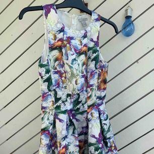En jättefin blommig klänning utsvängd nedtill , med dragkedja baktill ! Helt ny me etikett på!  Köparen står för frakten!