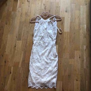 Vit klänning endast använd en gång. Öppen i ryggen med en knytning vit typ nacken/skuldrorna