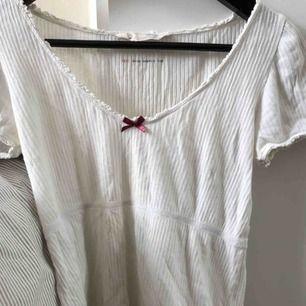 Jättesöt vit Odd Molly t-shirt/topp med en lila rosett över bröstet, använd knappt 2 gånger och passar både XS och S då den är stretchig:)