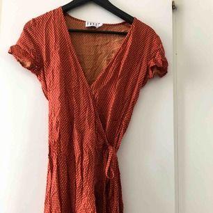 Söt rödorange prickig omlott klänning från NA-KD använd endast en gång på en avslutningsmiddag! Köpt för 399kr ! :)
