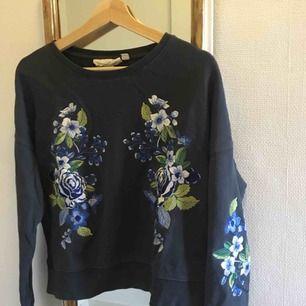 Superfin grå tröja med blåa/vita blommor på från H&M!! Säljer då den tyvärr inte används särskilt mycket. Den är i strl S! Köparen står för frakt☺️