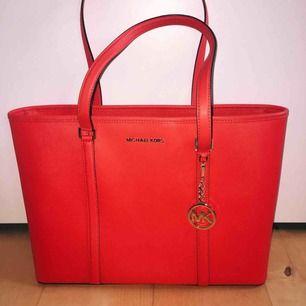 Michael Kors-väska i röd färg med guld detaljer. Köpt i New York för 4700kr, knappt använd. Har 4 mindre fack samt ett större fack innanför samt ett fack på baksidan utanför. Den kan stängas med dragkedja. :)