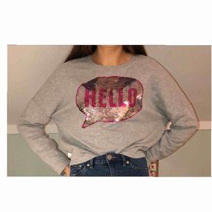 """Grå tröja från New Yorker med texten """"Hello"""" om du drar uppåt och """"Bye"""" om du drar neråt. Ingen paljett saknas så alla sitter kvar."""