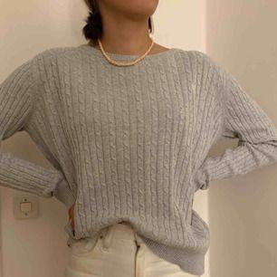 Grå Kabelstickad tröja från ginatricot. Storlek enligt lapp är XL men skulle säga att den passar M. Köparen står för frakten :)