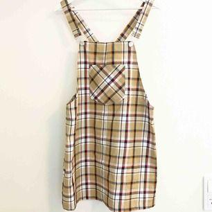Fin hängselklänning. Helt oanvänd, prislapp o knappar sitter kvar.  Mycket skönt o strechigt material!