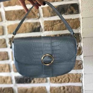 Säljer denna ljusblåa väska från NA-KD eftersom att jag har råkat beställa en likadan fast röd. Väldigt fin, man kan ta av banden om man vill och det tillkommer 2 band.