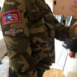 Militärgrön jacka ifrån bikbok med coola märken. Storlek S men passar även M. Modellen på jackan är kort.