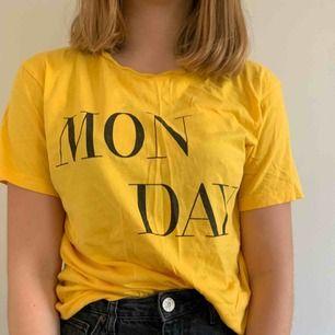 """Säljer en fin gul T-shirt med trycket """"MONDAY"""" Säljer på grund av att den inte kommer till användning. Kan mötas upp i Helsingborg men annars står köparen för frakten"""