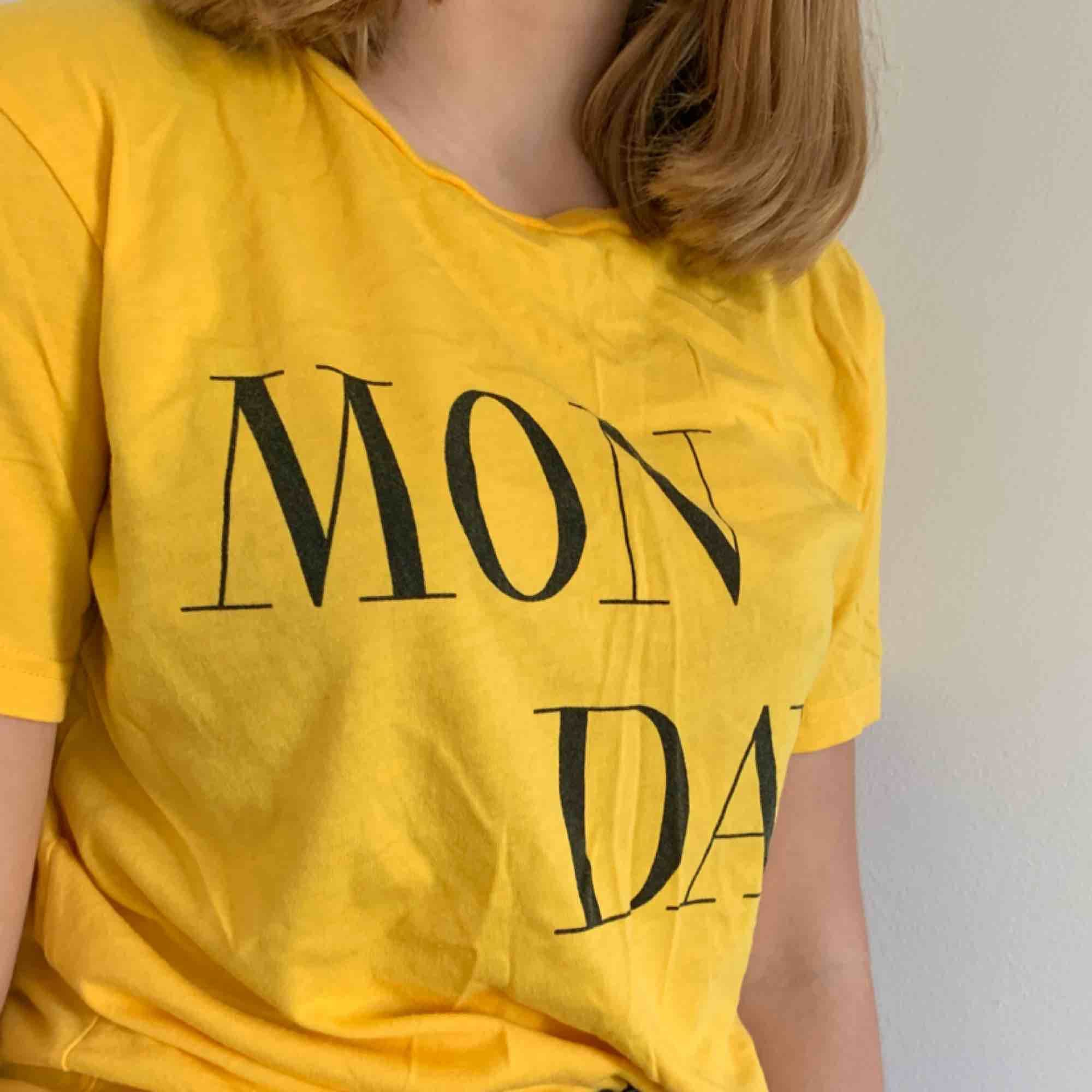 """Säljer en fin gul T-shirt med trycket """"MONDAY"""" Säljer på grund av att den inte kommer till användning. Kan mötas upp i Helsingborg men annars står köparen för frakten. T-shirts."""