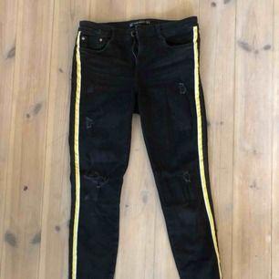 Ett par tighta svarta jeans med en gul rand på sidan av benet, jeansen har även lite slitningar på knän och lår. Väldigt balla!