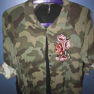 Ganska oanvänd blus/skjorta. Cool militär känsla med tryck på ryggen Köparen står för frakt