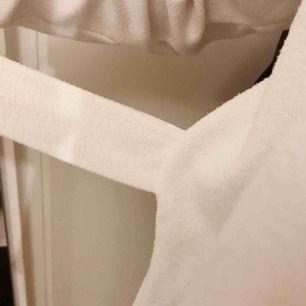 Vit lite varmare tröja med snören som går att knyta båda fram och bak