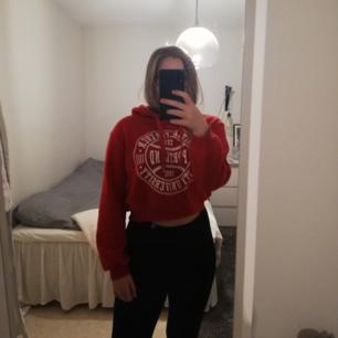 Croppad röd hoodie med snyggt vitt tryck fram! Använd några gånger men inga slitningar eller liknande. Fri frakt! Hör gärna av dig vid Intresse!