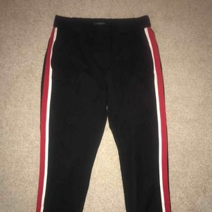 Svarta kostymbyxor från Zara med röd/vit revär på sidan. Knappt använda, bra skick. Lite kortare modell, slutar lite ovanför ankeln. Storlek S - 120kr exkl frakt