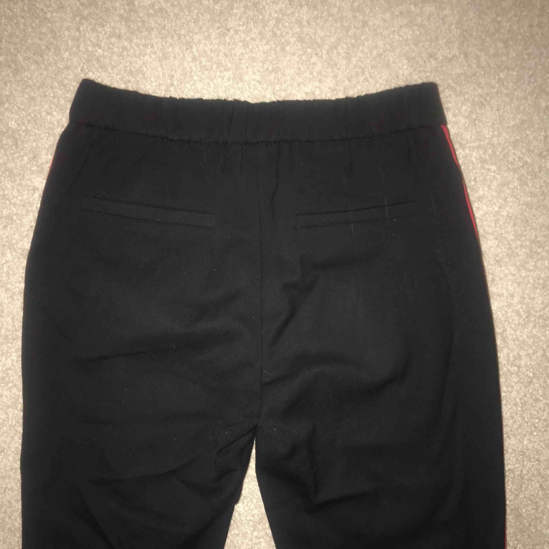 Svarta kostymbyxor från Zara med röd/vit revär på sidan. Knappt använda, bra skick. Lite kortare modell, slutar lite ovanför ankeln. Storlek S - 120kr exkl frakt. Jeans & Byxor.