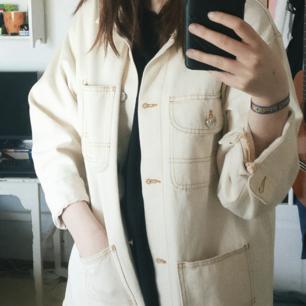 En beige jeansjacka med kontrastsömmar i ockra. 100% bomull. Färgen är mest lik på bilden når jag har den på.