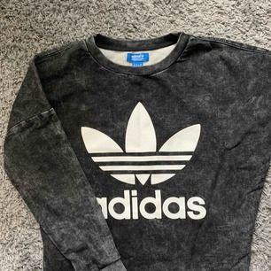 Sweatshirt från Adidas. Svart/grå melerat mönster med avklippt detalj nedtill. Frakt tillkommer.