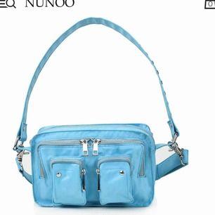 En blå nunoo väska som sällan är använd. Man får med ett långt band, men det sitter fast ett lite kortare. Färgen gör sig inte rättvisa på dom sista två bilderna, eftersom ljuset går åt andra hållet. Men färgen är iaf som den första bilden