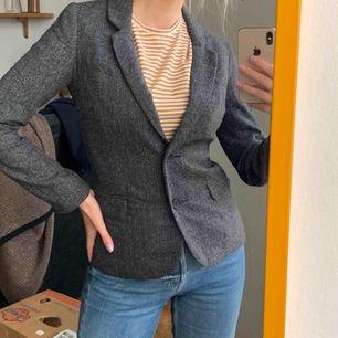 """Grå Kavaj med små blå streck inblandat i tyget. Har även två armbåge-""""pads"""" som ger den en brittisk look! Frakt : 59kr ✨❣️ samfraktar gärna med andra produkter jag säljer"""