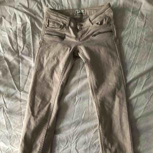 Beiga jeans med dragkedjor fram