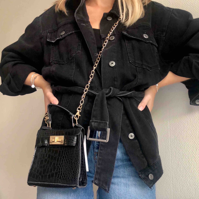 Säljer denna lilla, praktiska väska med krokodileffekt och gulddetaljer🐊 Aldrig använd. Avtagbar guldkedja medföljer. Hör gärna av dig om du är intresserad eller har några frågor🌷. Väskor.