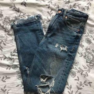 """momjeans från H&M med slitningar och """"girls bite back"""" skrivit i rött under ena fickan. sparsamt använda!"""