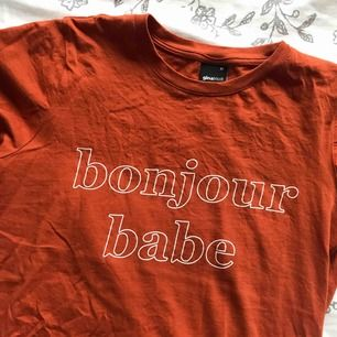 """tshirt från gina i orange/brun färg. trycket säger """"bonjour babe"""". fint skick"""