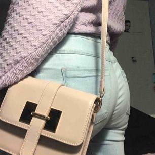 En elegant axelrem väska i dammrosa med guldfärgade detaljer. Väskan har en  ficka på insidan som är detaljerad med guld dragkedja. Det ända att se upp för är insidan av väskan som har par små rosa läppstiftsfläckar, men de syns knappt.