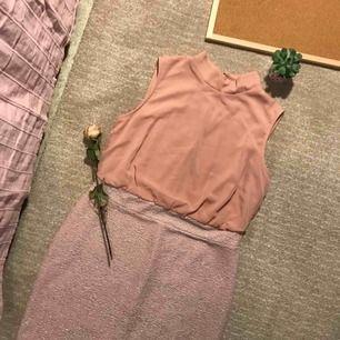 Smutsrosa klänning i knälägnd med skrimmrande nederdel. Överdelan passar löst, nederdelen är tajtare. Modellen i bilden har S storlek och har på sig klänningen i storlek M.