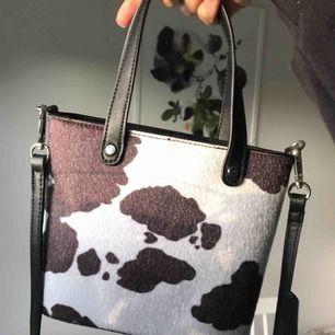 Asball komönstrad bucketväska ifrån Asos!🐄 Älskar den med hela mitt hjärta, men har aldrig kommit till användning Köparen står för frakt!