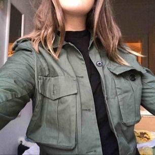 Storlek 40 men mer som 36/38. Croppad jacka i militär grön färg med två framfickor. Använd fåtal gånger