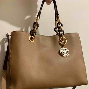 Sparsamt använd Michael Kors väska i läder från 2016. Ljus brun/beige färg. Gulddetaljer, handtag och axelrem.  Knappt använt denna väska, endast fåtal gånger så skicket är väldigt bra. Förvaringspåse kommer med.  Nypris var 3500. Inga skambud tack :)