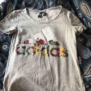 Grå adidas T-shirt med blommig text! Inte den vanligaste adidas tröjan så därför unik på sitt sätt🌸🌼 frakt tillkommer på 30kr